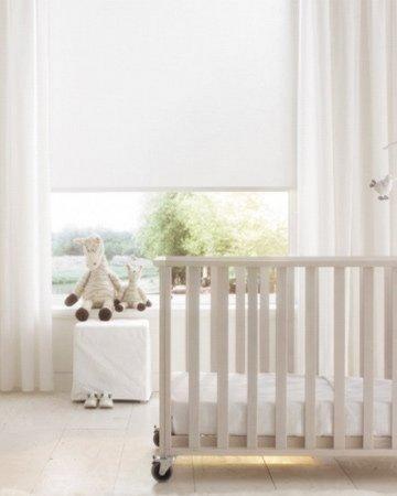 witte babykamer met witte gordijnen en rolgordijn